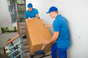 men moving a box down the stairs